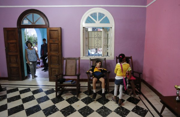 Students sit in rocking chairs in the hallway of the Cuban School of Foreign Languages.
