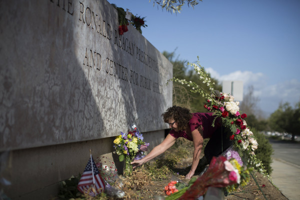 Image: Monika Poach arranges flowers left in memory of former first lady Nancy Reagan