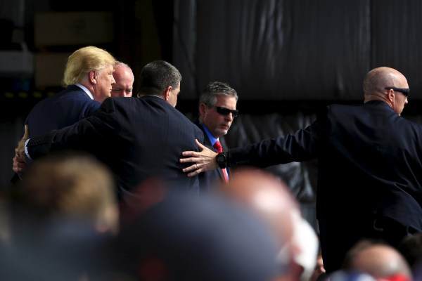 Image: Secret Service agents surround U.S. Republican presidential candidate Trump during a disturbance as he speaks at Dayton International Airport in Dayton, Ohio