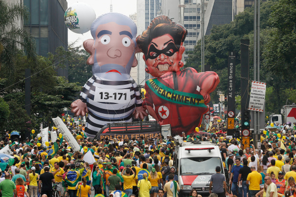 Image: Demonstrators parade large inflatable dolls depicting Brazil's former President Luiz Inacio Lula da Silva