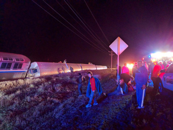 Image: Passengers gather after a train derailed near Dodge City