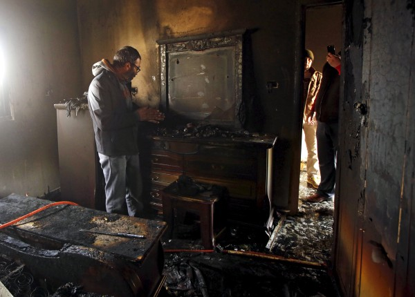 Image: Palestinian man inspects the damage to the torched house of Ibrahim Dawabsheh, the main witness in the July arson attack, in the West Bank village of Duma