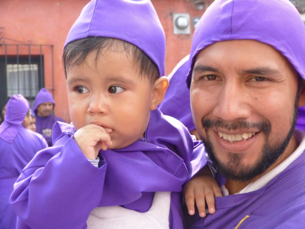Father and son dressed as the shrouded carriers known as cucuruchos.
