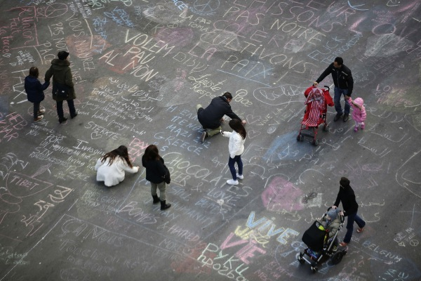 Image: People write messages on the ground at Place de la Bourse