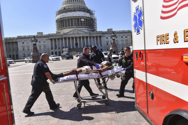 Image: Police and EMS personnel transport the person believed to be the gunman away from the shooting scene at the U.S. Capitol