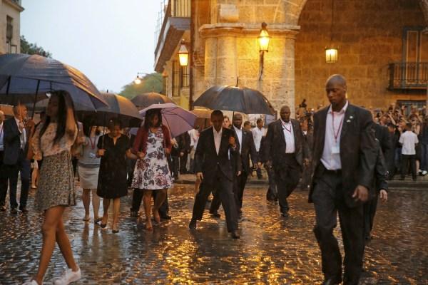 Image: U.S. President Barack Obama steps over a puddle while touring Old Havana