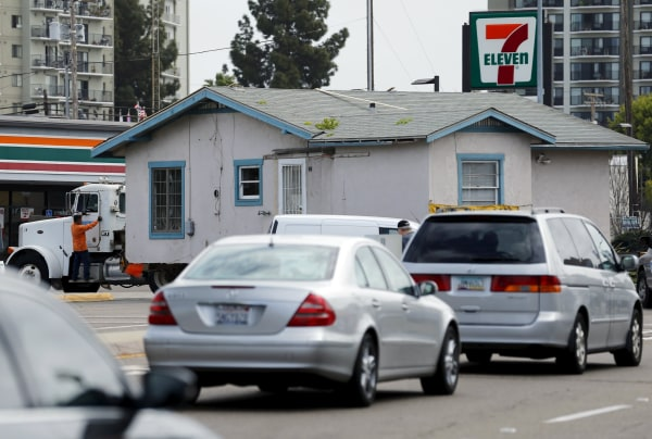 Image: A house makes a turn on a city street as its moved by truck for recycling and resale from a neighborhood in San Diego