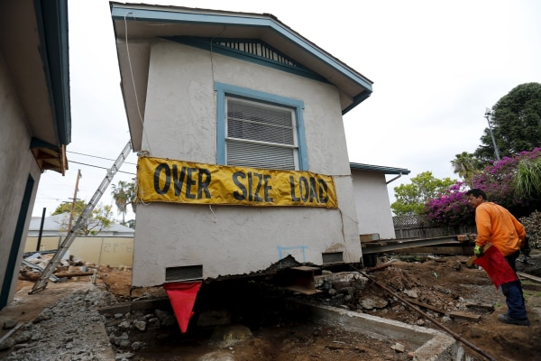 Image: Workers prepare to move an old home for recycling and resale from its neighborhood in San Diego