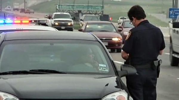 Police officer writing a ticket for a traffic violation.