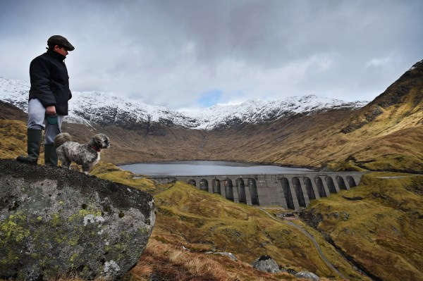 Image: A boy and his dog view Cruachan hydro electric power station in Dalmally, Scotland
