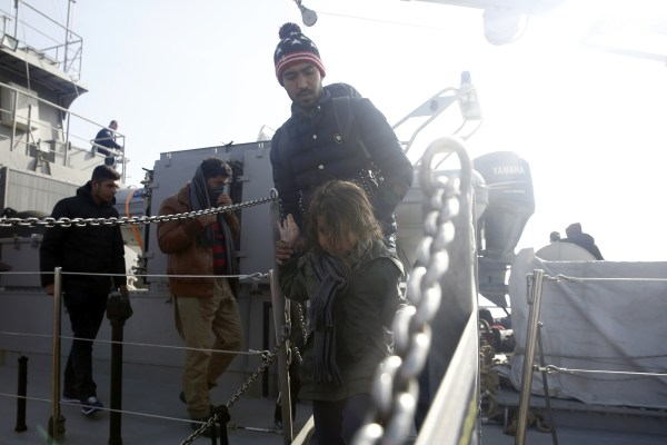 Image: A child disembarks a Greek Coast Guard vessel at the port of Mytilene