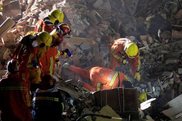Image: Rescue workers search at the site after a three-storey residential building collapsed in Shanghai