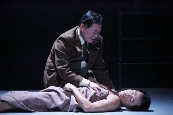 """George Takei kneels over Trieu Tran in East West Player's 2005 production of """"Equus."""""""