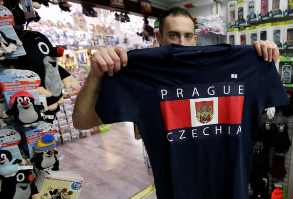 Image: A vendor displays a t-shirt with a sign Czechia in a souvenir gift shop in central Prague