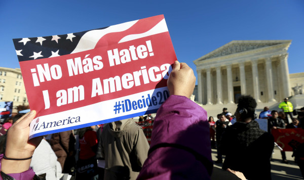 Image: A protester holds a sign as immigrants and community leaders rally in front of the U.S. Supreme Court in Washington