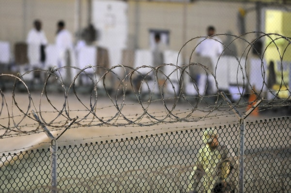 Image: File photo of a Navy guard patrolling Camp Delta's detainee recreation yard during the early morning at Guantanamo Bay naval base