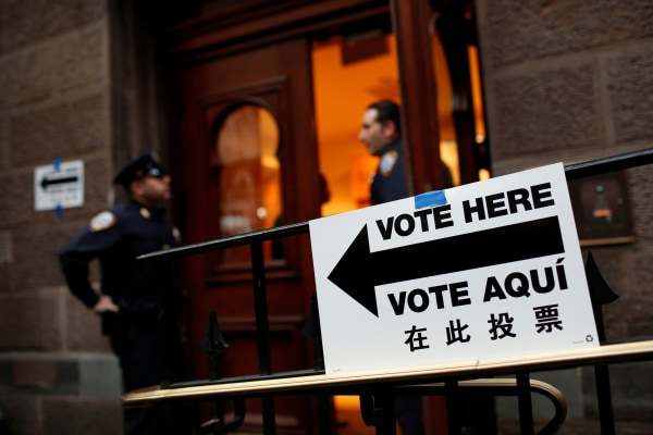 Image: Members of the New York police guard an entrance at a polling station as voting opened for the New York primary elections in the Manhattan borough of New York City