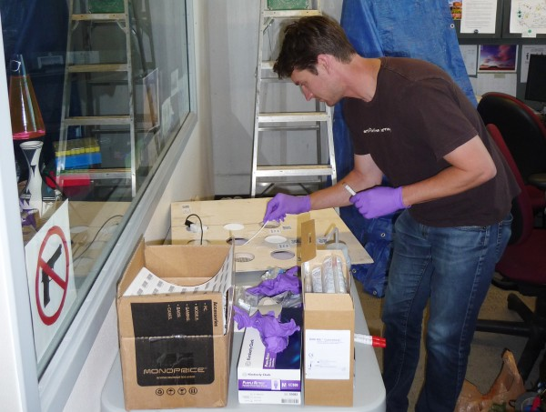 Image: Researcher John Chase samples office surface materials just prior to installation