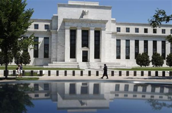 File image of the U.S. Federal Reserve is reflected in car as security officer patrols front of building in Washington