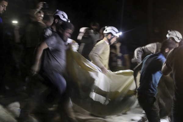 Image: A victim is carried from the hospital in Aleppo, Syria
