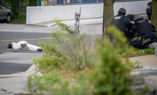 Image: A man, claiming to have a bomb, lies in the street outside of the Fox45 television station, which was evacuated due to a bomb threat, in Baltimore
