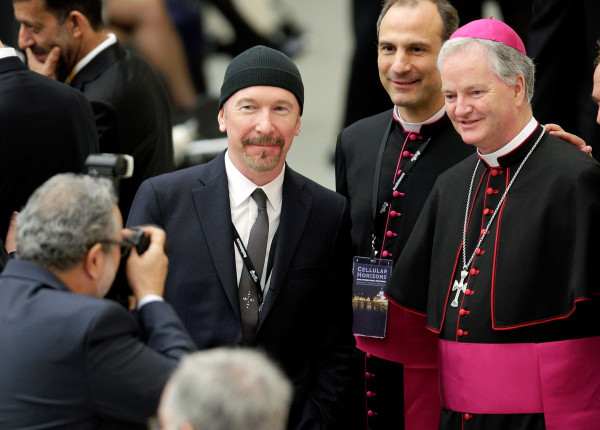 Image: U2 guitarist David Evans poses with Irish bishop Paul Tighe.