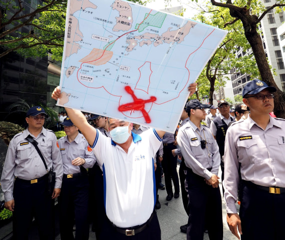 Image: A fisherman holding map showing location of Image: Map showing Okinotori in Taipei on April 27