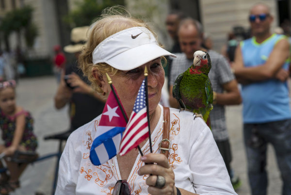 A cruise passenger poses for a photo with a parrot in Havana