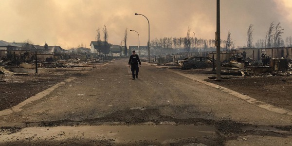 Image: A Mountie surveys the damage on a street in Fort McMurray.