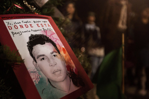 People gather around Christmas tree decorated with pictures of 43 missing students