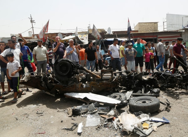 Image: People gather at the scene of a car bomb attack in Baghdad