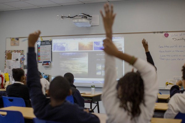 Students raise their hands in a classroom.
