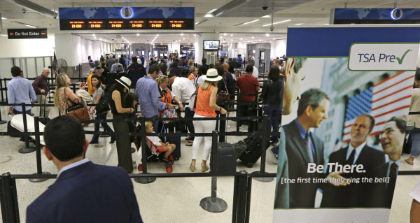 Image: Travelers stand in line as they prepare to pass through a TSA checkpoint