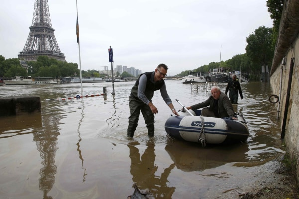 Image: A man uses a dinghy as he leaves his houseboat moored near the Eiffel towel during flooding on the banks of the Seine River in Paris