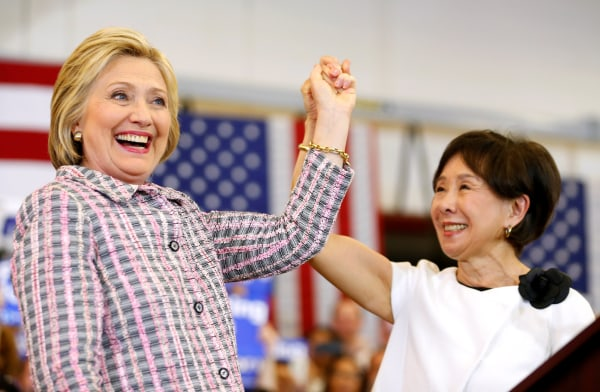 Image: U.S. Democratic presidential candidate Hillary Clinton holds up the hand of congresswoman Doris Matsui during a campaign stop in Sacramento, California