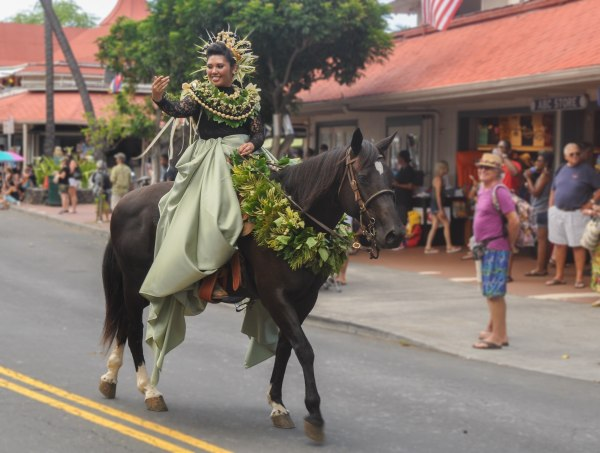 Cheyenne Fuerte, the pa'u princess representing the Island of Moloka'i at the 2016 Kona-Kailua's King Kamehameha Day Celebration Parade. Fuerte's leis are made of kukui nut and her pa'u attire is green, which represents the flora and colors of that island