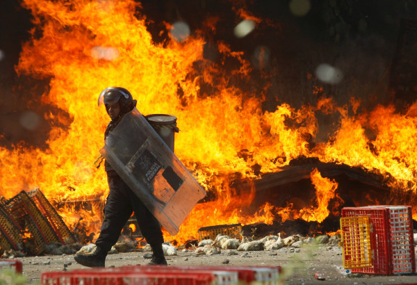 Image: A riot police officer walks past a burned truck