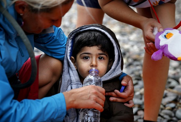 Image: Volunteers give water and toys to an exhausted Syrian refugee child soon after he and his family arrived on the Greek island of Lesbos
