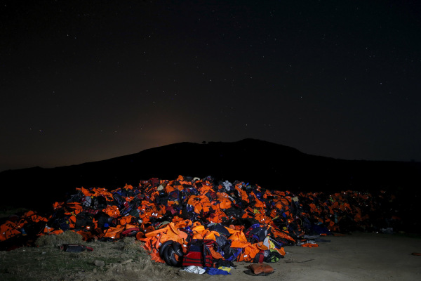 Image: A long exposure photo shows thousands of lifejackets left by migrants and refugees, piled up at a garbage dump site on the Greek island of Lesbos