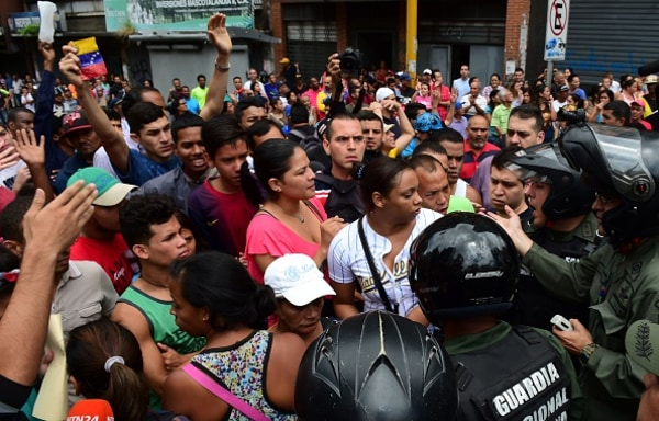 File Photo: People argue with members of the National Guard as they try to line in front of a supermarket in Caracas on June 2, 2016.
