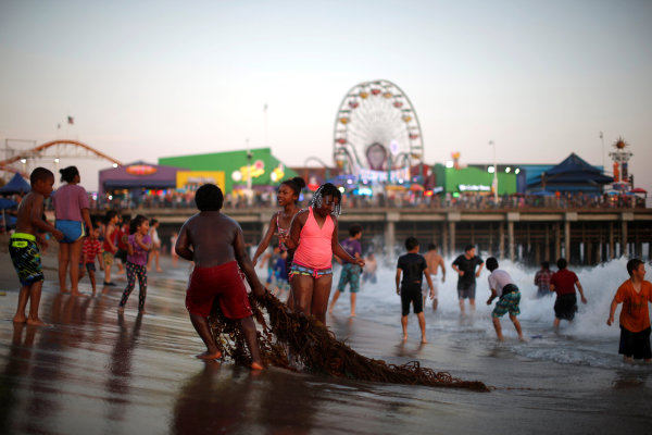 Image: People cool off in the Pacific Ocean during a record-setting heat wave across the U.S. Southwest, on the summer solstice in Santa Monica