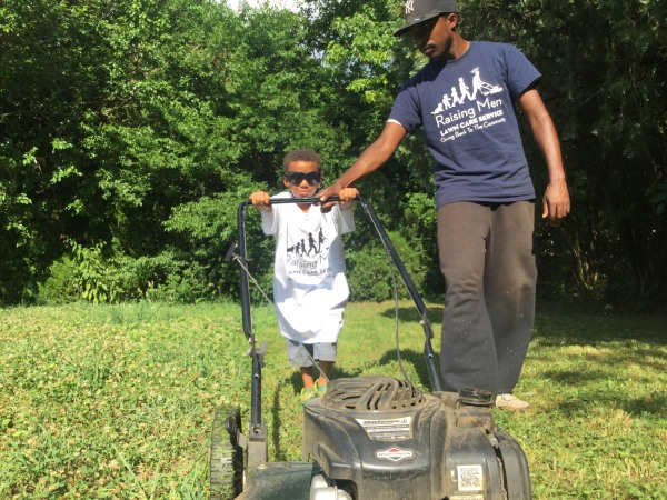 Image: Rodney Smith, Jr., helps a young volunteer with Raising Men Lawn Care give back to his community