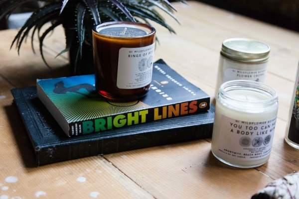 "Tanwi Nandini Islam's novel ""Bright Lines"" next to Hi Wildflower Botanica's candles"