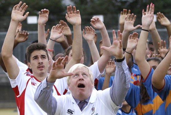Image: London Mayor Boris Johnson jumps for the ball during a rugby coaching session at Haverstock School in London