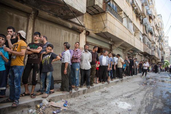 Image: Syrians queue up to buy bread in Aleppo