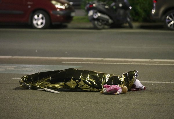 Image: A body is seen on the ground after at least 30 people were killed in the southern French town of Nice when a truck ran into a crowd celebrating the Bastille Day national holiday