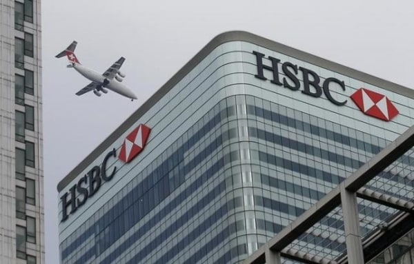 A Swiss International aircraft flies past the HSBC headquarters building in the Canary Wharf financial district in east London