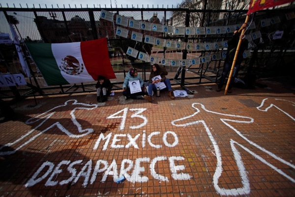 Demonstrators sit next to a graffiti during a protest against the visit to Argentina by Mexico's President Pena Nieto in Buenos Aires.