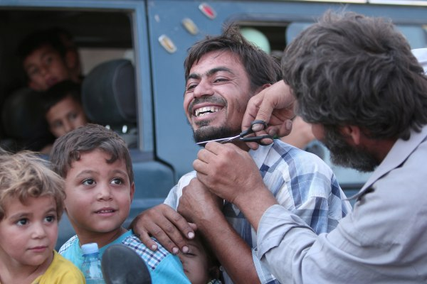 Image: A man cuts the beard of a civilian who was evacuated with others by the Syria Democratic Forces (SDF) fighters from an Islamic State-controlled neighbourhood of Manbij