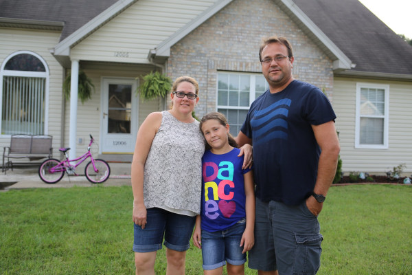 Juan Carlos Labaut and his family stand in front of their home on the outskirts of Louisville.